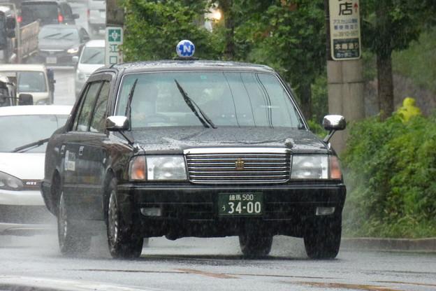 写真: 雨の上り坂をあがる「黒タク」