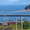 写真: 海辺を走る真っ赤な電車